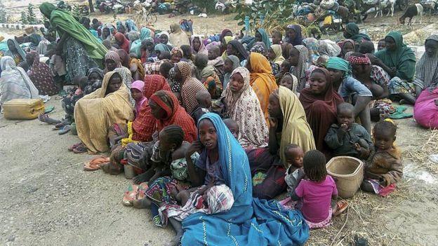 Mulheres (com véus coloridos sob a cabeça) e crianças sentadas no chão