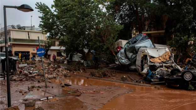 Car wreckages are piled up in a flooded street of Mandra, northwest of Athens