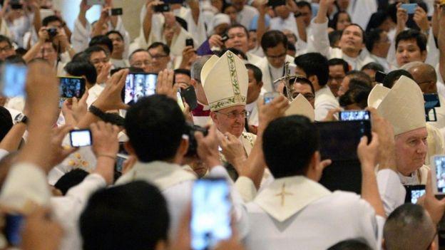Una aglomeración de gente que toma fotos del Papa Francisco