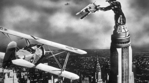 Un fotograma de la película King Kong en el que aparece atacando aviones desde la cima del Empire State Buliding.