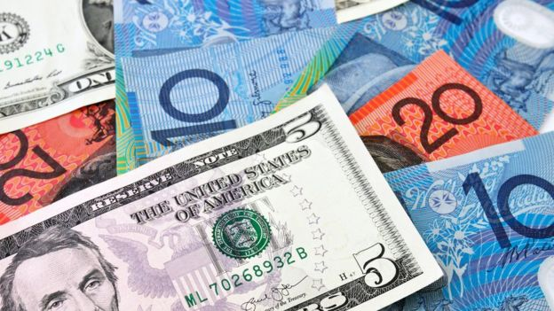 A US $5 note sits on top of a stack of Australian currency