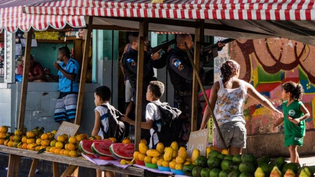policiais fazem mira com armas de alto calibre apesar da presença de crianças ao redor