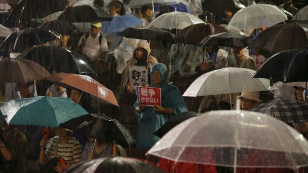 Protesters holding umbrellas and wearing raincoats gather at a rally against Japanese Prime Minister Shinzo Abe and his security bill