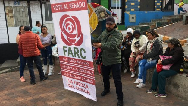 A man holds up a banner urging to vote for the Farc