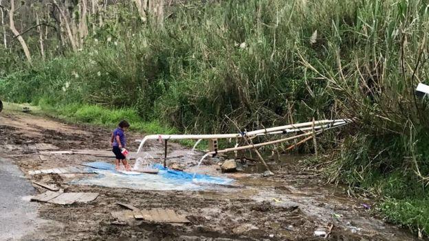 Una niña recoge agua de la ladera de una montaña en Puerto Rico.