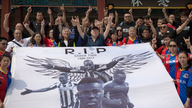 Beijing Enterprises club football fans show a banner that reads 'RIP Cheick Tiote 1986-2017' ahead of a memorial service for Cheick Tiote in Beijing on June 13, 2017.