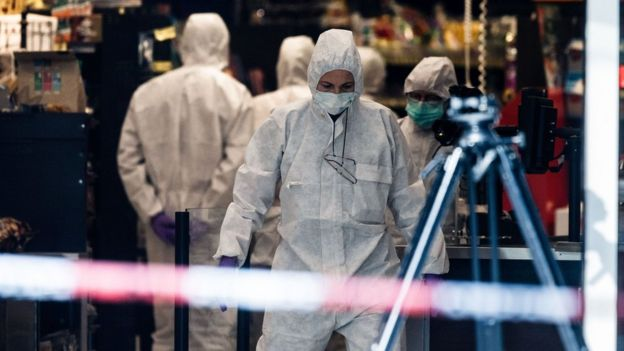 Police investigators gather evidence at a supermarket in the northern German city of Hamburg, where a man killed one person and wounded several others in a knife attack, 28 July 2017