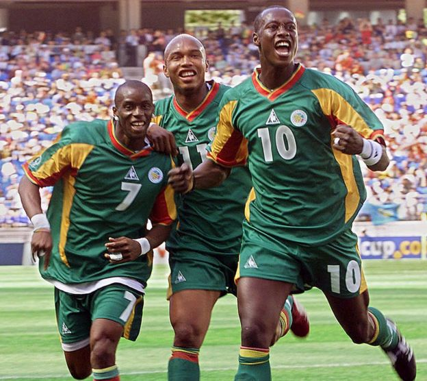 Senegalese defender Khalilou Fadiga (R) celebrates his goal from a penalty kick with teammates Henri Camara (L-#7) and El Hadj Diouf (C) in their Group A match against Uruguay at the 2002 FIFA World Cup Korea/Japan in Suwon, 11 June 2002.