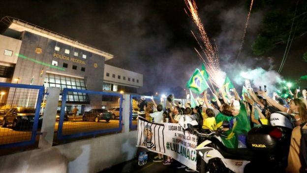Anti-Lula demonstrators celebrate as former Brazilian President Luiz Inacio Lula da Silva arrives at the Federal Police headquarters, in Curitiba, Brazil