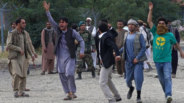 People shout slogans at the scene of three bombings that targeted the funeral of a victim of the violent protests in Kabul