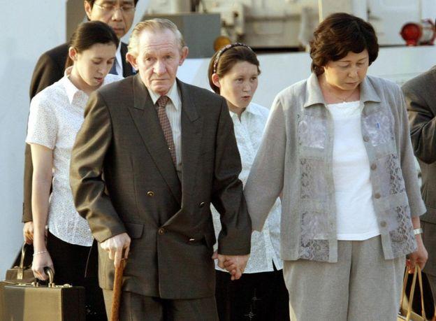 Hitomi sostiene de la mano a su frágil marido, seguidos de sus hijas en el aeropuerto internacional de Tokio, en 2004