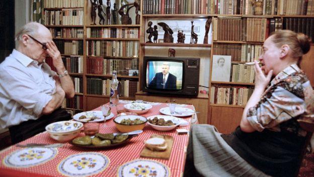 Москвичи Юрий и Елена Пудаловы смотрят обращение Бориса Ельцина к народу. Март 1993 года, на столе маринованные огурцы и колбаса.