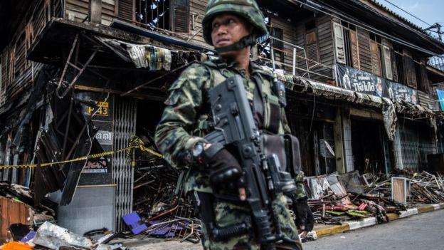 ทหารยืนหน้าบ้านที่ได้รับความเสียหาย