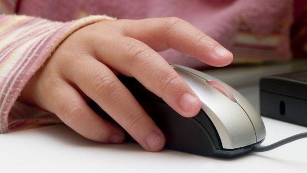 Criança usa mouse do computador