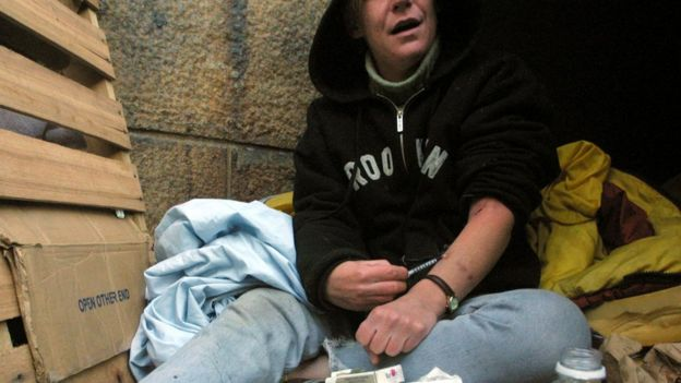 A homeless woman injects herself with heroin