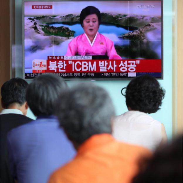 La gente se agolpa en Tokio para ver cómo Ri Chun-hee, la inconfundible presentadora de noticias de Corea del Norte, anuncia el lanzamiento de un nuevo misil el 4 de julio de 2017.