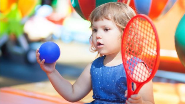Girl about two years old with a racket and a ball