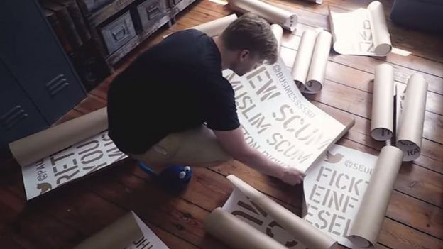 Shahak Shapira pictured in a screengrab from his YouTube video, with the stencils he made to spray-paint the offensive tweets