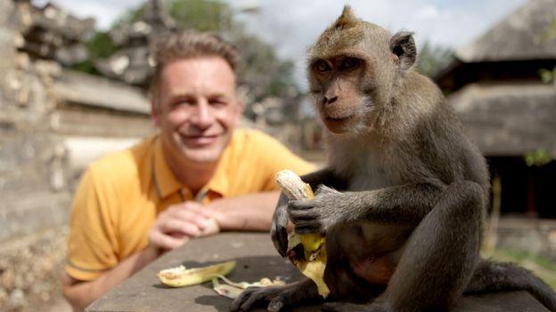 Chris Packman sonrie junto a un mono.