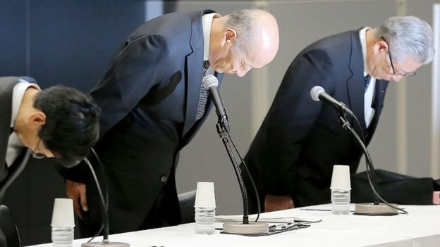 Tadashi Ishii (C), president of Japan's biggest advertising agency Dentsu, bowing with other executives during a press conference in Tokyo in December 2016
