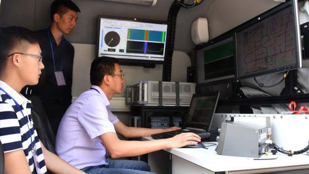 6月7日,在山东省济南中学高考考点,3名济南市无线电管理办公室的工作人员在车内进行无线电监测工作。