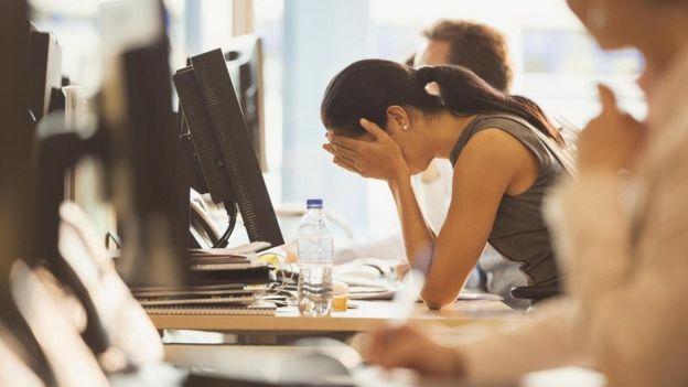 Una persona cubriéndose el rostro con las manos, apoyada en un escritorio en la oficina