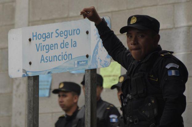 Policía apoyado en un cartel que dice Hogar Seguro Virgen de la Asunción el 15 de marzo de 2017.