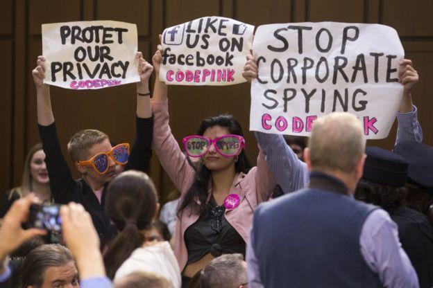 Pessoas seguram cartazes protestando contra falta de privacidade no Facebook