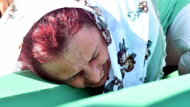 Una mujer llora desconsolada sobre el féretro que lleva los restos de un familiar asesinado en Srebrenica