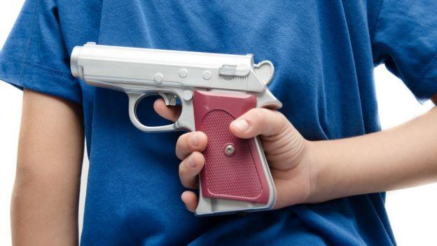 Um menino segura uma arma de brincadeira