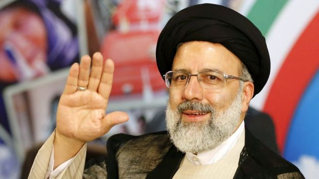 Ebrahim Raisi with hand raised in greeting