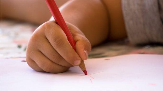 Un niño haciendo garabatos en un papel con un creyón rojo