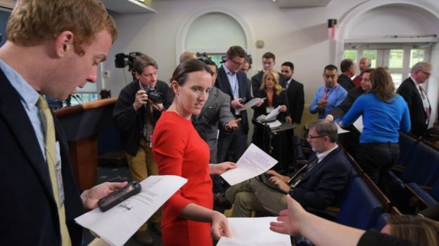 Deputy Press Secretary Lyndsey Walters hands out documents to reporters in the White House, advising them that there will be no further on camera statements, after US President Donald Trump sacked FBI Director James Comey on May 9, 2017
