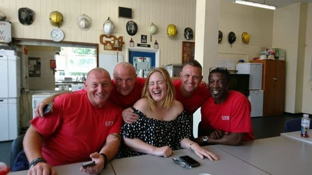 Picture of a laughing Adele with firefighters