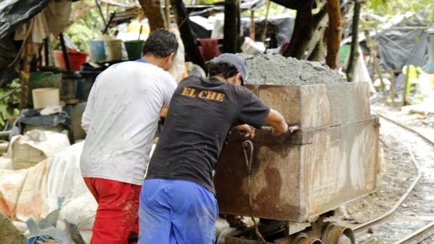 Dos hombres empujan un carro con material de mina.