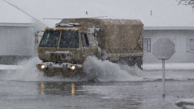 A National Guard vehicle patrols streets in flooded Massachusetts