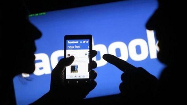 Dos personas ven en un móvil el muro de Facebook.