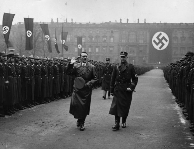 Adolf Hitler walks past two files of guardsman in front of a huge swastika at a parade at the Lustgarten, Berlin in 1936