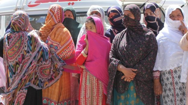 Relatives of the victims of a mass killing look on