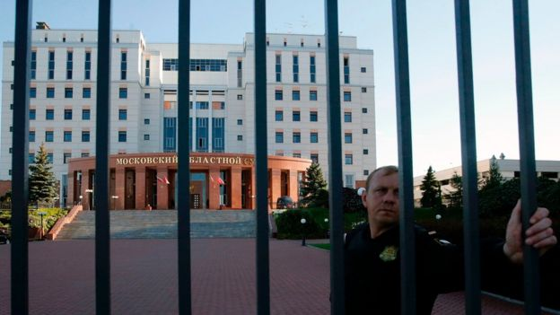 A convoy guard stands behind a fence around the building of the Moscow Regional Court outside Moscow
