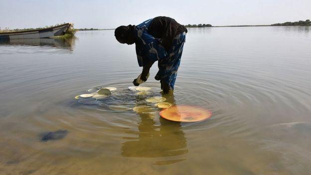 Mujer lavando unos platos en el lago Chad.