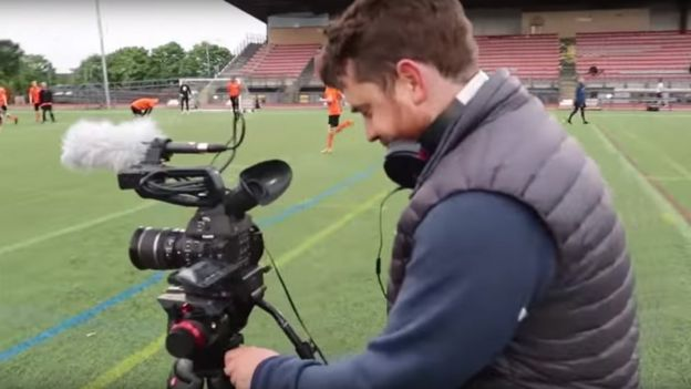 Camera crew setting up on pitch