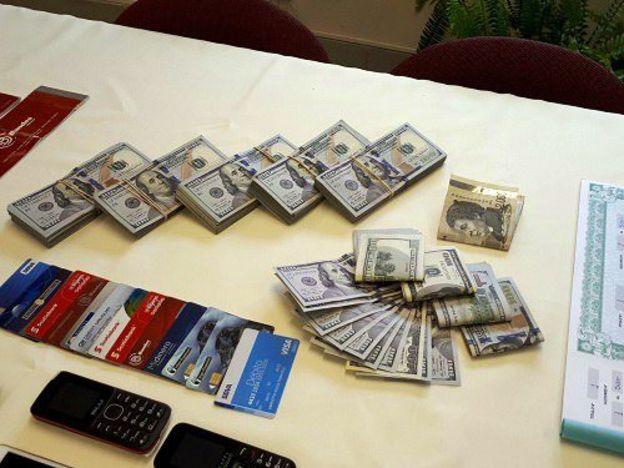 Pilhas de dólares, cartões de crédito, celulares e identidades falsas confiscados