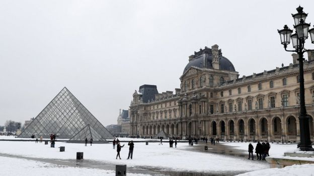 Tourists walk in the snow at the Louvre Pyramid in Paris February 9, 2018.