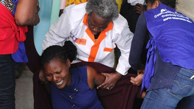 A relative is comforted by emergency medical staff at Moi Girls School in Nairobi, after a fatal pre-dawn blaze gutted one of the boarding facilities at the school leading to several deaths, 2 September 2017