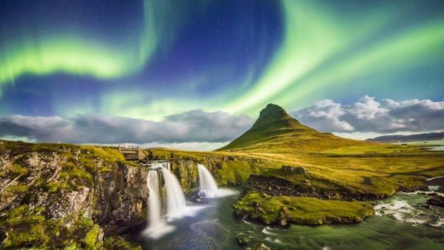 aurora sobre Kirkjufell y las cascadas aledañas en Islandia de noche.