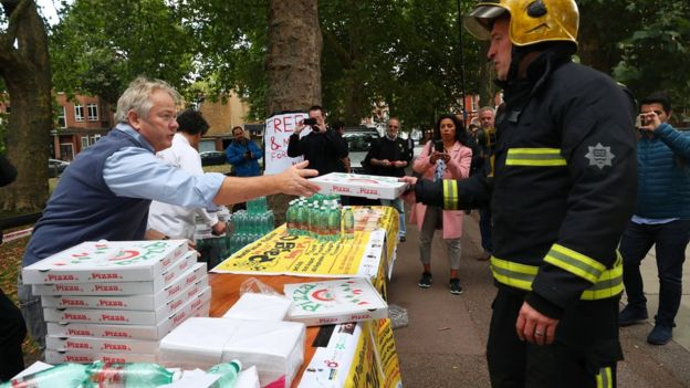 Pizzas and water being handed out