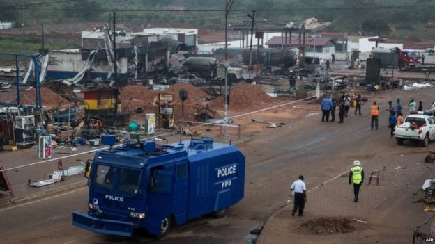 A police vehicle drives on the site of an explosion in Accra on October 8, 2017 a day after a gas tanker caught fire, triggering explosions at two fuel stations