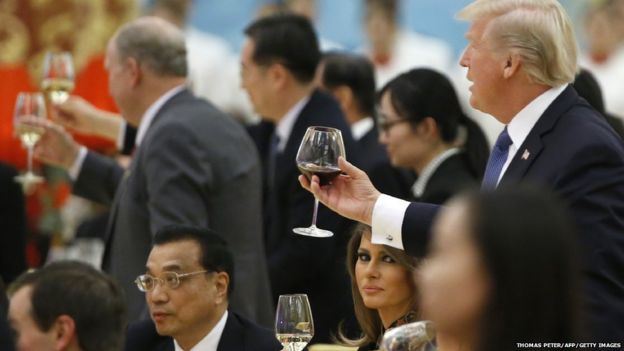 President Donald Trump raising a toast while his wife Melania sits by his side