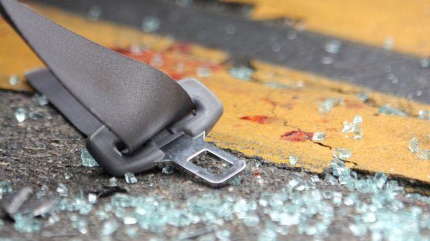 Cacos de vidro e cinto de segurança no asfalto